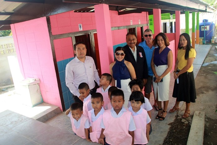 The PSC team, teachers and children pose for a photo in front of the renovated restrooms.