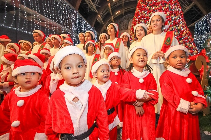 Little children dressed in their bright red Santa suites join the older children as they get ready to sing Christmas Carols.