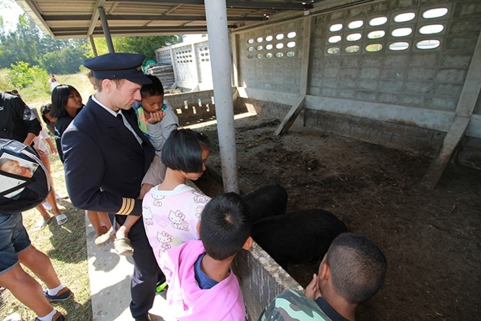 A Lufthansa co-pilot mingles with the appreciative children while checking out the ham on hooves in the facility's pig pen.