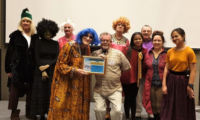 MC Bob Smith, who is also a member of Pattaya Players, presents the PCEC's Certificate of Appreciation to the Pattaya Players' cast for their very entertaining pantomime. From left to right, Gary Hougen (Fiddle), Wendy Khan (The Witch), Andrew Murphy (The King), Chris Harman (Ugly Sister and also the Director), MC Bob Smith, Doug Campbell (Ugly Sister), Aom Konchan (Buttons and ballerina), Charles Elwin (Prince Charming), Mara Swankey (Dandini), and Caidie Brennan (Cinderella).