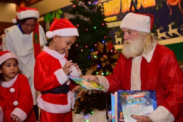 Santa Claus a.k.a. Rick Bevington gives a Christmas present to a little child.