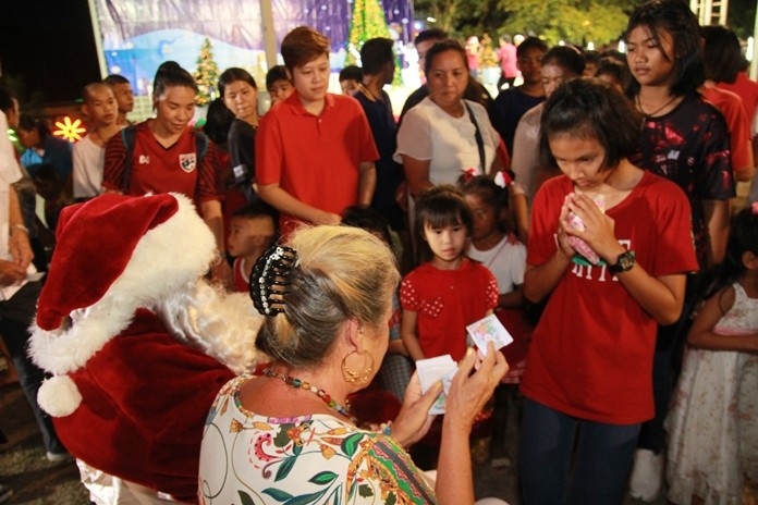 Children line up respectfully to accept gifts from generous benefactors.