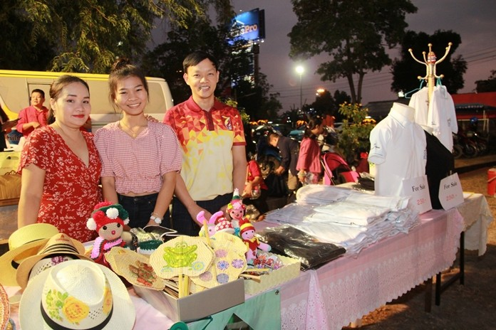 Drop-In Manager Pirun Noyimjai (right) visits one of the many booths set up for children and staff to sell the foundation's products.