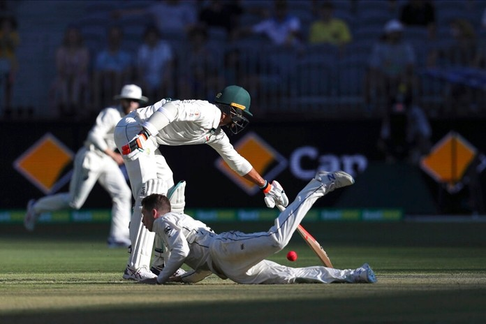 Australia's Mitchell Starc, left, reaches for the crease as New Zealand's Mitchell Santer dives for the ball during their cricket test match in Perth, Australia, Friday, Dec. 13, 2019. (AP Photo/Trevor Collens)