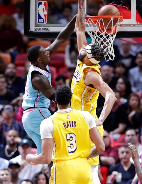 Miami Heat guard Kendrick Nunn, left, shoots as Los Angeles Lakers guard Kentavious Caldwell-Pope defends during the first half of an NBA basketball game, Friday, Dec. 13, 2019, in Miami. (AP Photo/Lynne Sladky)