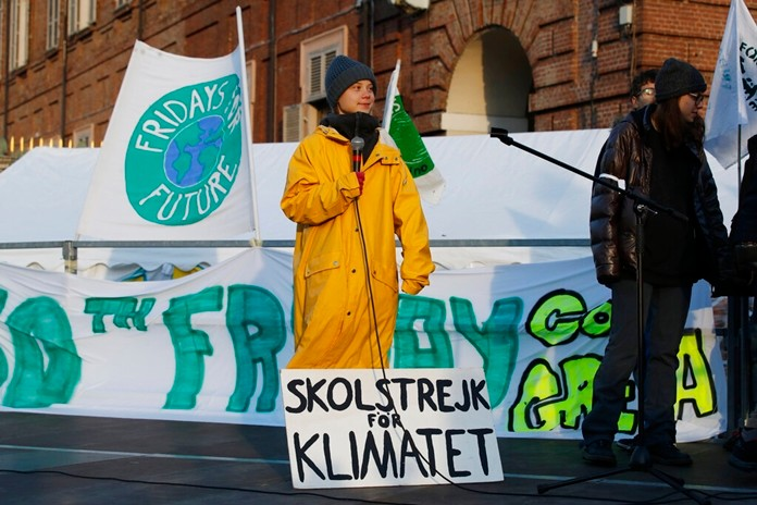 "Swedish environmental activist Greta Thunberg, with a sign reading in Swedish ""School strike for the climate"", attends a climate march, in Turin, Italy, Friday. Dec. 13, 2019. (AP Photo/Antonio Calanni)"