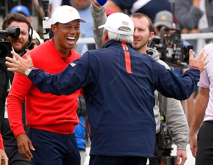 U.S. team player and captain Tiger Woods, left, celebrates with vice captain Fred Couples after Woods won his singles match during the President's Cup golf tournament at Royal Melbourne Golf Club in Melbourne, Sunday, Dec. 15, 2019. (AP Photo/Andy Brownbill)