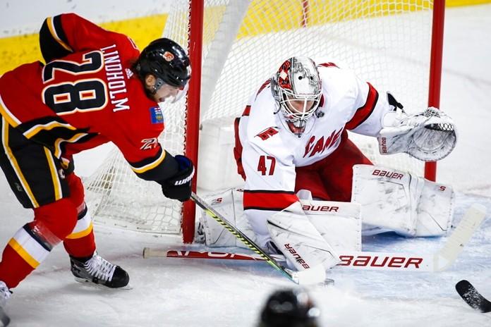 Carolina Hurricanes goalie James Reimer, right, blocks the net against Calgary Flames' Elias Lindholm during first-period NHL hockey game action in Calgary, Alberta, Saturday, Dec. 14, 2019. (Jeff McIntosh/The Canadian Press via AP)