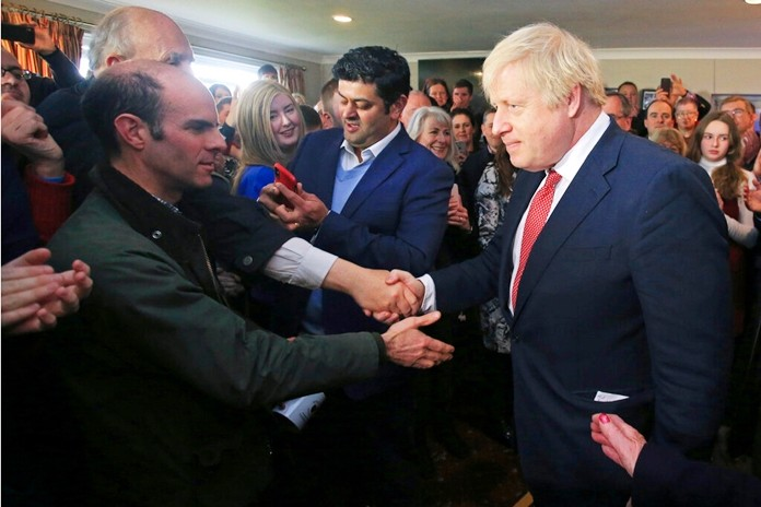 Britain's Prime Minister Boris Johnson shakes hands with supporters on a visit to meet newly elected Conservative party MP for Sedgefield, Paul Howell at Sedgefield Cricket Club in County Durham, north east England, Saturday Dec. 14, 2019, following his Conservative party's general election victory. (Lindsey Parnaby/Pool via AP)