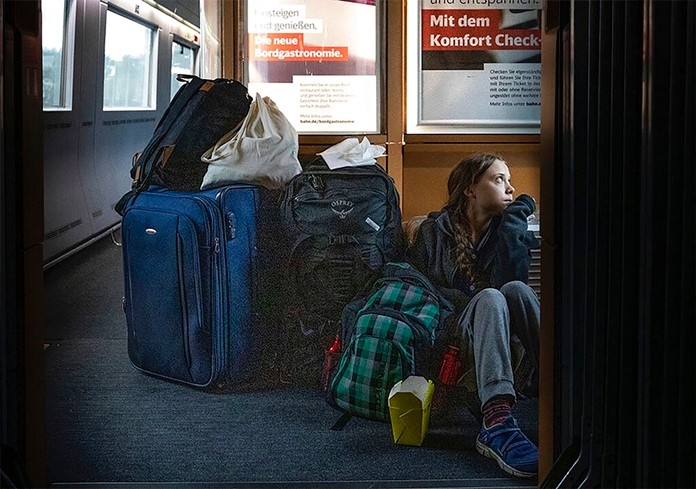 """In this image taken from Twitter feed of Climate activist Greta Thunberg, showing Thunberg sitting on the floor of a train surrounded by bags Saturday Dec. 14, 2019, with the comment """"traveling on overcrowded trains through Germany. And I'm finally on my way home!"""" (Twitter @GretaThunberg via AP)"""