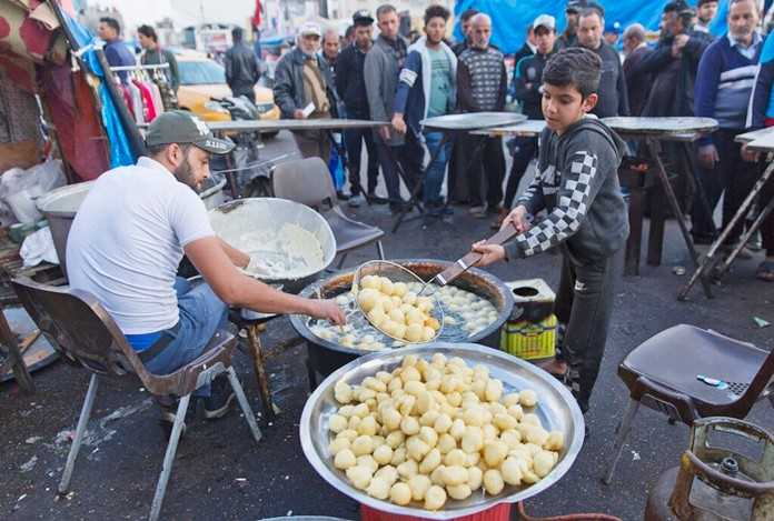 In this photo taken Sunday, Dec. 8, 2019, a volunteer chef prepares to serve free portions of the popular sweets of Awamah, fried dough balls, to protester in the center of Baghdad, Iraq. (AP Photo/Nasser Nasser)