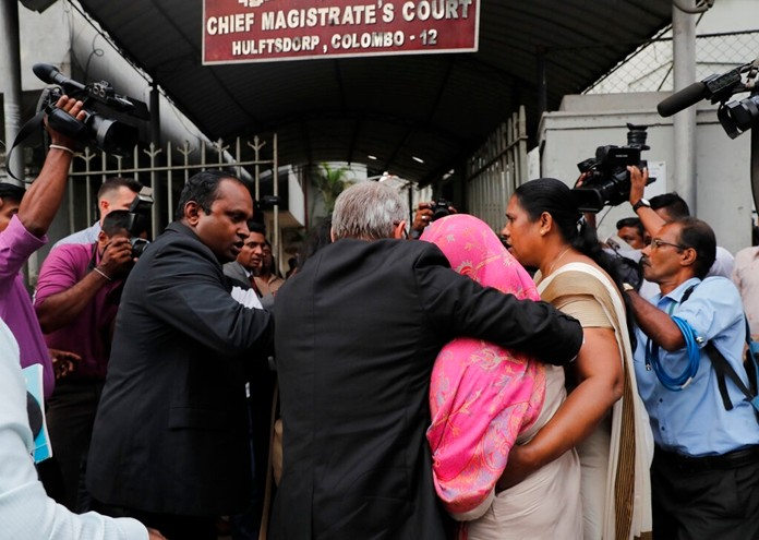 Sri Lankan Swiss embassy worker Garnier Banister Francis, covered in pink shawl, holds on to an unidentified foreign national as Sri Lankan police officers escort her to a magistrate court after her arrest in Colombo, Sri Lanka, Monday, Dec. 16, 2019. (AP Photo/Eranga Jayawardena)