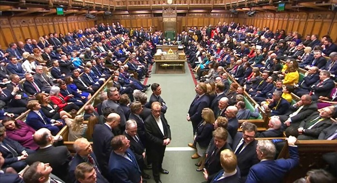 In this image taken from video, members of UK Parliament return to the House of Commons, London, Tuesday Dec. 17, 2019. (House of Commons via AP)