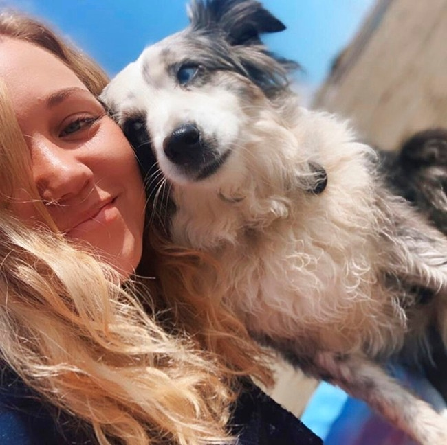 This undated selfie photo provided by Emilie Talermo showing Emilie Talermo and her dog Jackson taken in San Francisco, Calif. Talermo, is offering a $7,000 reward for her blue-eyed miniature Australian Shepherd stolen from outside a grocery store. (Emilie Talermo via AP)