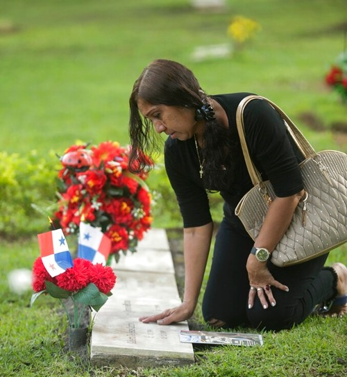 A woman touches the grave of a person who died during the 1989 U.S. military invasion that ousted Panama's strongman Manuel Noriega, at Jardin de Paz cemetery in Panama City, Friday, Dec. 20, 2019. (AP Photo/Arnulfo Franco)