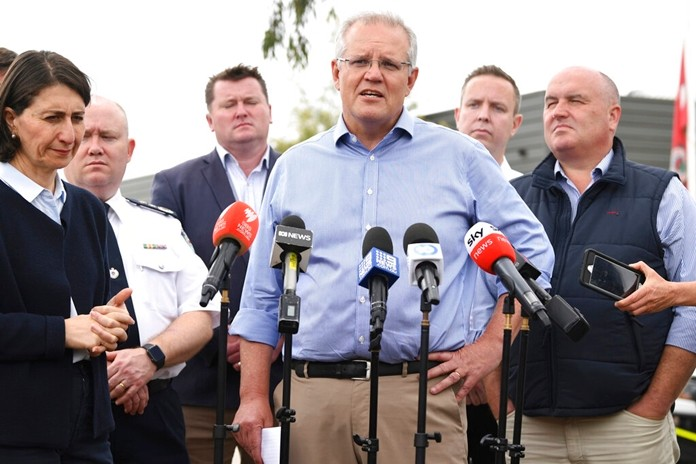 Australia's Prime Minister Scott Morrison, with NSW Premier Gladys Berejiklian, left, speaks to the media during a visit to the Wollondilly Emergency Control Centre in Sydney, Sunday, Dec. 22, 2019. (Joel Carrett/AAP Images via AP)