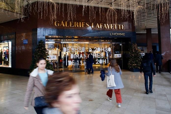 Pedestrians walk in front of the Galeries Lafayette department store in Paris, Thursday, Dec.19, 2019. (AP Photo/Thibault Camus)
