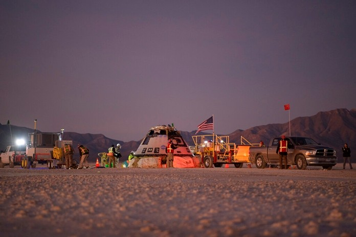 Boeing, NASA, and U.S. Army personnel work around the Boeing Starliner spacecraft shortly after it landed in White Sands, N.M., Sunday, Dec. 22, 2019.(Bill Ingalls/NASA via AP