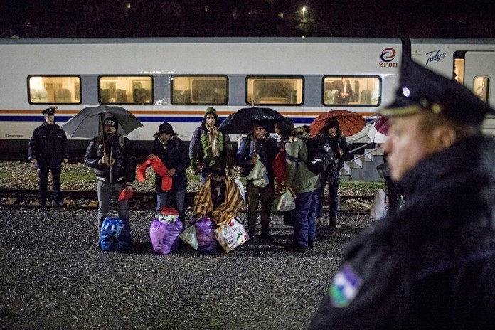 In this picture taken Saturday Dec. 14, 2019, a group of Pakistani migrants stands by the rail tracks after being taken off a train bound to the town of Bihac by Bosnian police in BosanskaKrupa, northwestern Bosnia. (AP Photo/Manu Brabo)