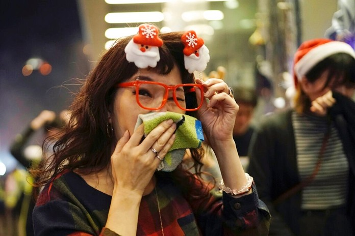 A woman wearing Christmas decorations in her hair reacts to tear gas as police confront protesters on Christmas Eve in Hong Kong on Tuesday, Dec. 24, 2019.(AP Photo/Kin Cheung)