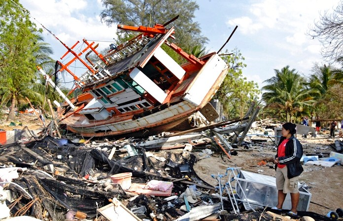 In this Jan. 5, 2005, file photo, NatayaPumsi, 36, tries to sort out what to do with the boat that landed on and destroyed her home after her village of Ban Nam Khem was hit by last weeks tsunami in KhaoLak in southern Thailand. (AP Photo/Richard Vogel)
