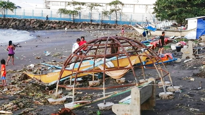 Residents walks beside an outrigger and playground equipment that were damaged by Typhoon Phanfone along a coastline in Ormoc city, central Philippines on Thursday Dec. 26, 2019. The typhoon left over a dozen dead and many homeless. (AP Photo)