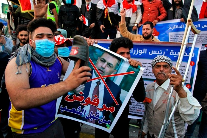 """A protester hits a poster with a defaced picture of Asaad al-Eidani, Iran-backed parliamentary bloc's nominee for the post of the prime minister and Arabic that reads """"rejected by the people,"""" with a shoe during anti-government demonstrations in Baghdad, Iraq, Thursday, Dec. 26, 2019. (AP Photo/Khalid Mohammed)"""