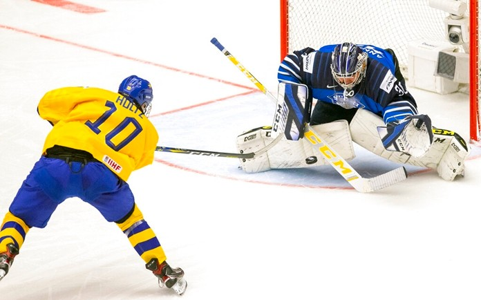 Alexander Holtz of Sweden, left, shoots against goalkeeper Justus Annunen of Finland during the World U20 Ice Hockey Championships Group A match between Sweden and Finland in Trinec, Czech Republic, Thursday Dec. 26, 2019. (Vladimir Prycek/CTK via AP)