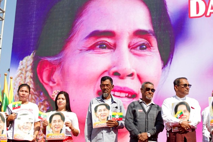 In this Tuesday, Dec. 10, 2019 file photo, Members of Myanmar Muslims community hold portraits of Myanmar leader Aung San Suu Kyi to pray as they gather in front of City Hall in Yangon, Myanmar.(AP Photo/Thein Zaw, File)