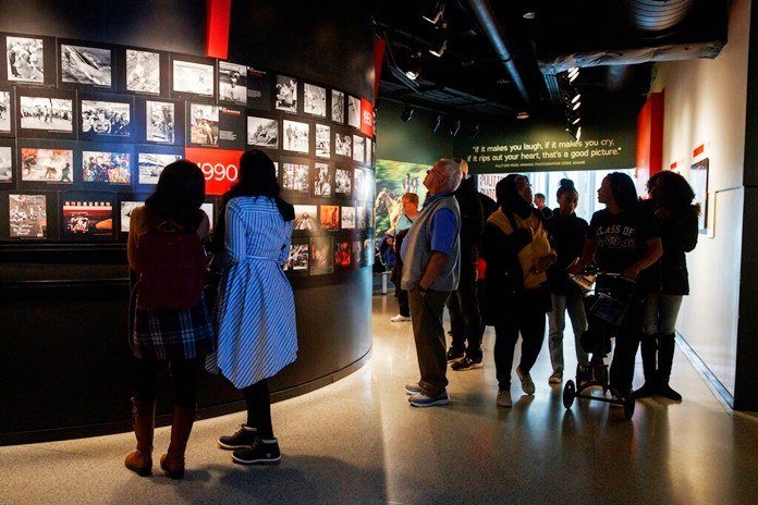 In this Friday, Dec. 20, 2019, photo, people visit the Pulitzer Prize Photography exhibition at the Newseum, in Washington. (AP Photo/Jacquelyn Martin)
