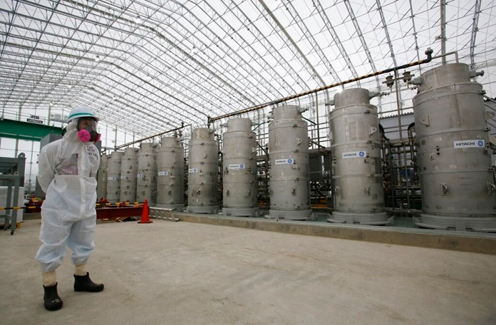 In this Nov. 12, 2014, file photo, a Tokyo Electric Power Co. (TEPCO) official wearing a radioactive protective gear stands in front of Advanced Liquid Processing Systems during a press tour at the Fukushima Dai-ichi nuclear power plant in Okuma, Fukushima Prefecture, northeastern Japan. (AP Photo/Shizuo Kambayashi, Pool, File)