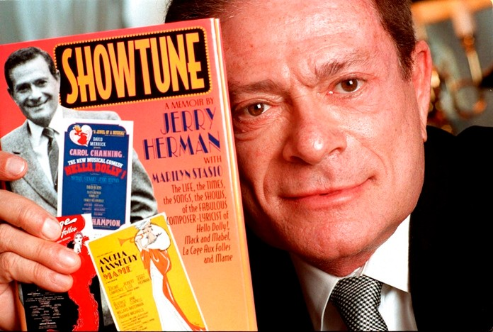 """In this Nov. 19, 1996, file photo, composer Jerry Herman displays his book """"Showtune,"""" in New York. (AP Photo/Jim Cooper, File)"""