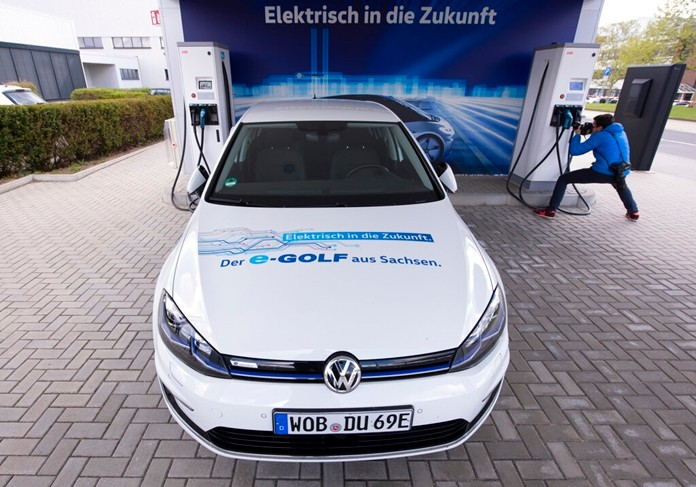"In this Tuesday, May 14, 2019 file photo an e-Golf car stands at the charging station during a press tour of the plant of the German manufacturer Volkswagen AG (VW) in Zwickau, Germany. Automaker Volkswagen is raising the bar for its plunge into battery powered cars, saying it will reach its goal of 1 million e-autos per year two years earlier than planned. The slogans read: "" Electric into the future - The e-Golf from Saxonia'. (AP Photo/Jens Meyer)"