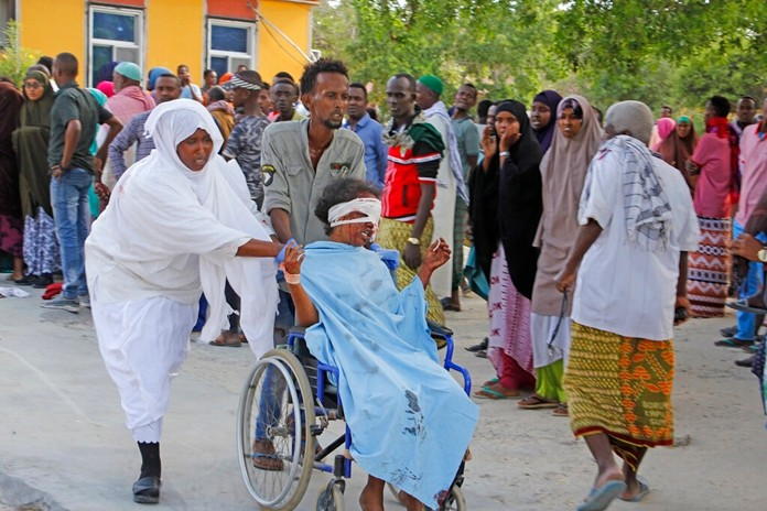 A civilian who was wounded in suicide car bomb attack is helped to be taken to hospital in Mogadishu, Somalia, Saturday, Dec, 28, 2019. (AP Photo/Farah AbdiWarsame)