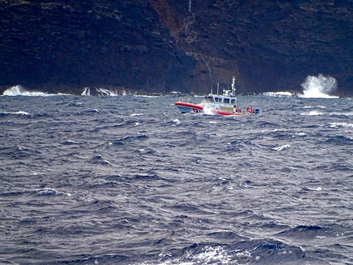 In this photo released by the U.S. Coast Guard, a coast guard vessel searches along the Na Pali Coast on the Hawaiian island of Kauai on Friday, Dec. 27, 2019, the day after a tour helicopter disappeared with seven people aboard. (Lt. j.g. Daniel Winter/U.S. Coast Guard via AP)
