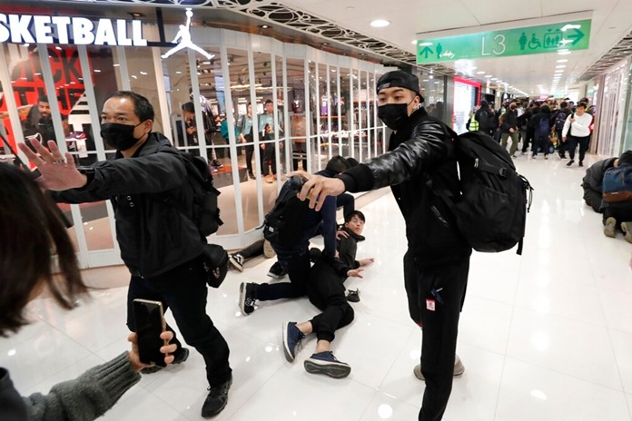 An undercover policeman points a can of pepper spray as others detain a protester during a demonstration at a shopping mall popular with traders from mainland China near the Chinese border in Hong Kong, Saturday, Dec. 28, 2019. (AP Photo/Lee Jin-man)