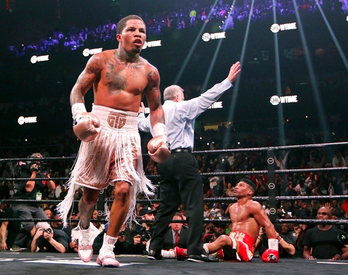 Gervonta Davis, left, heads to the corner as Yuriorkis Gamboa, right, looks up at referee Jack Reiss during the WBA secondary lightweight title boxing bout early Sunday, Dec. 29, 2019, in Atlanta. Davis won when the fight was stopped in the 12th round. (AP Photo/Tami Chappell)