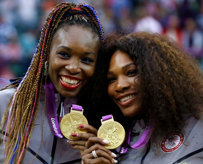 This Aug. 5, 2012, file photo shows Venus Williams, left, and Serena Williams of the United States showing their gold medals in women's doubles at the All England Lawn Tennis Club in Wimbledon, London at the 2012 Summer Olympics. Williams has been voted the AP Female Athlete of the Decade for 2010 to 2019. (AP Photo/Elise Amendola, File)