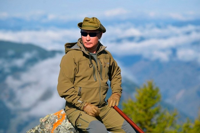 In this undated file photo released by Russian Presidential Press Service, Russian President Vladimir Putin rests on a hill in Siberia during a break from state affairs ahead of his birthday. (Alexei Druzhinin, Sputnik, Kremlin Pool Photo via AP, File)