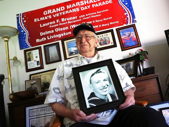 In this Nov. 17, 2016, file photo, Lauren Bruner, a survivor of the USS Arizona which was attacked on Dec. 7, 1941, holds with a 1940 photo of himself at his home in La Mirada, Calif. (AP Photo/Reed Saxon, File)