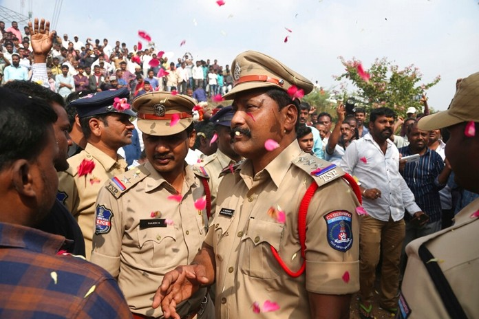 People throw flower petals on the Indian policemen guarding the area where rape accused were shot, in Shadnagar some 50 kilometers or 31 miles from Hyderabad, India, Friday, Dec. 6, 2019. (AP Photo/Mahesh Kumar A.)
