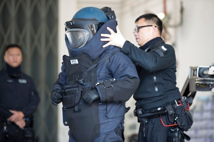 A police officer from the bomb disposal squad putting on protective gear during a demonstration for media in Hong Kong, Friday, Dec. 6, 2019. (AP Photo/Vincent Thian)