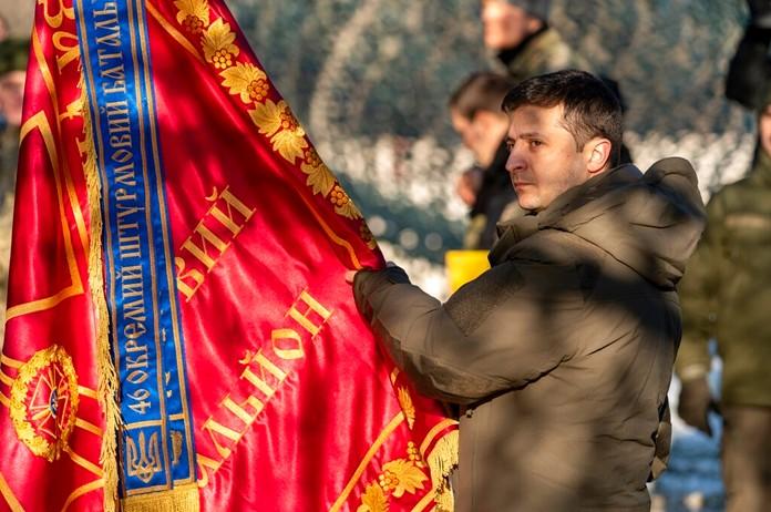 Ukrainian President Volodymyr Zelenskiy, hands over the flag of a military unit during his visits the war-hit Donetsk region, eastern Ukraine, Friday, Dec. 6, 2019. (Ukrainian Presidential Press Office via AP)