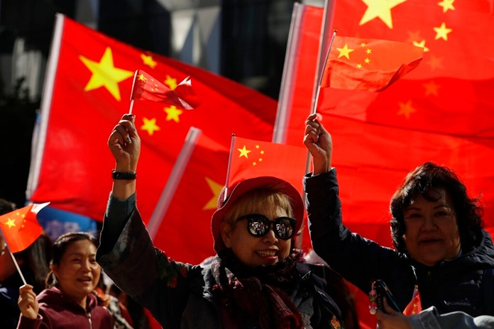 Pro-Beijing supporters wave the Chinese national flags during a rally in Hong Kong on Saturday, Dec. 7, 2019. (AP Photo/Mark Schiefelbein)