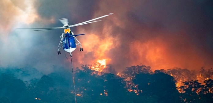 In this Monday, Dec. 30, 2019 photo provided by State Government of Victoria, a helicopter tackles a wildfire in East Gippsland, Victoria state, Australia. (State Government of Victoria via AP)