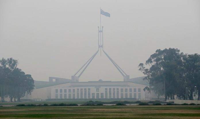 The Australian flag flies above Parliament House as smoke shrouds the Australian capital of Canberra, Australia, Wednesday, Jan. 1, 2020. (AP Photo/Mark Baker)