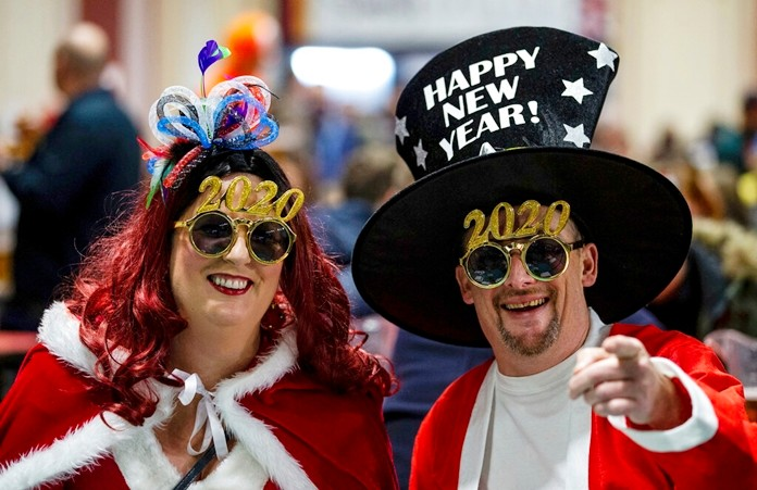Dart fans in fancy dress celebrating the New Year, during the Darts World Championships at Alexandra Palace, in London, Wednesday Jan. 1, 2020. (Steven Paston/PA via AP)