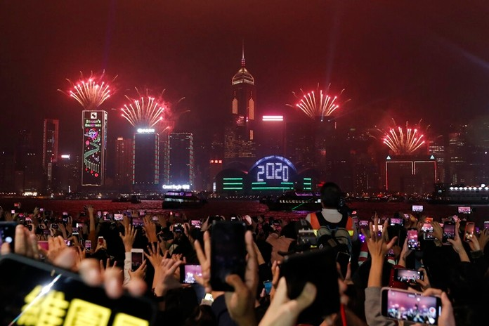New Year's fireworks light up the sky as protesters gather during a demonstration in Hong Kong, Tuesday, Dec. 31, 2019. (AP Photo/Lee Jin-man)