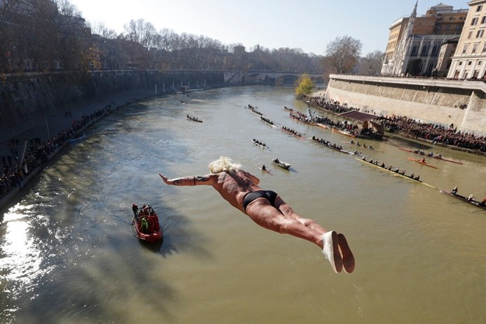 Maurizio Palmulli dives into the Tiber river from the 18 meters (59 feet) high Cavour Bridge in Rome, Wednesday, Jan. 1, 2020. (AP Photo/Andrew Medichini)