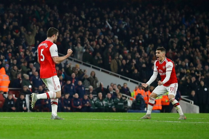 Arsenal's Sokratis Papastathopoulos, left, celebrates with teammate Lucas Torreira after scoring their side's second goal during the English Premier League soccer match between Arsenal and Manchester United at the Emirates Stadium in London, Wednesday, Jan. 1, 2020. Papastathopoulos scored once in Arsenal's 2-0 victory. (AP Photo/Matt Dunham)